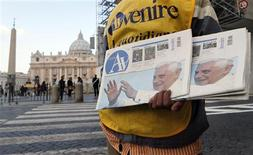 A newspaper seller shows newspapers with photographs of Pope Benedict XVI outside the Vatican February 17, 2013. Thousands of people are expected to gather in St. Peter's Square for Pope Benedict's Sunday Angelus prayer. REUTERS/Alessandro Bianchi
