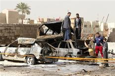 Residents gather at the site of a car bomb attack in the Ameen district in Baghdad February 17, 2013. A series of car bombs exploded in mainly Shi'ite neighbourhoods across the Iraqi capital Baghdad on Sunday, killing at least 20 people and wounding dozens, police and hospital sources said. REUTERS/Mohammed Ameen