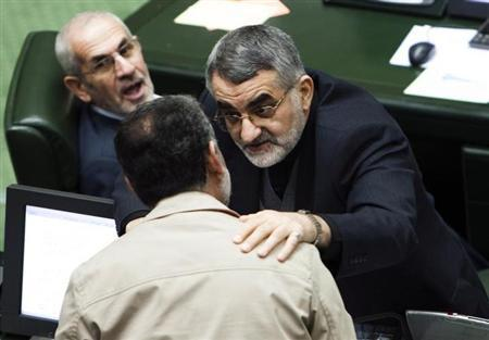 Alaeddin Boroujerdi (R) speaks with another Member of Parliament (MP) during a debate to reduce ties with Britain in Tehran November 27, 2011. REUTERS/Raheb Homavandi/Files