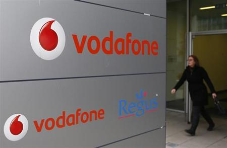 A woman walks past the logo of Vodafone company in Luxembourg in this picture taken on November 20, 2012. REUTERS/Francois Lenoir/Files