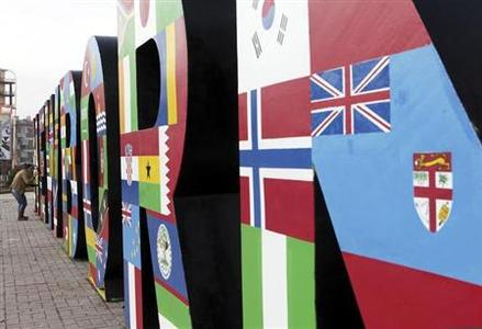 A woman paints a sign decorated with paintings of flags of the 98 countries that have recognised Kosovo's independence, in Pristina February 17, 2013. Kosovo marks the fifth anniversary of its independence from Serbia on Sunday. REUTERS/Hazir Reka