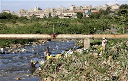 Women collect recyclable materials from the Nairobi river flowing past the Dandora Municipal Dumping Site in Kenya's capital Nairobi, April 8, 2011. REUTERS/Natasha Elkington/Files