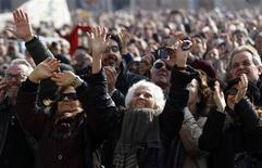 People wave as Pope Benedict XVI leads the Sunday Angelus in Saint Peter's Square at the Vatican February 17, 2013. Pope Benedict, speaking before a larger than usual crowd at his penultimate Sunday address, asked the faithful to pray for him and for the next pope. REUTERS/Alessandro Bianchi