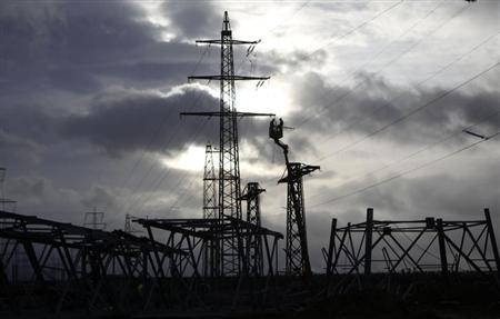Workers are silhouetted as they remove parts of a power pole to rebuild power lines in the western city of Meckenheim January 30, 2013. REUTERS/Ina Fassbender (GERMANY - Tags: ENERGY BUSINESS)