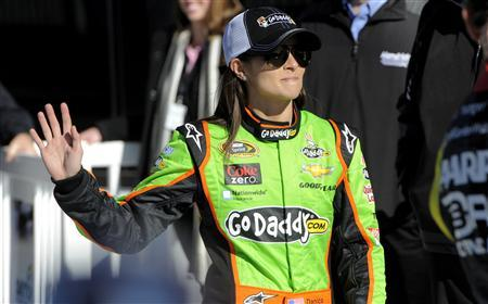 NASCAR Sprint Cup Series driver Danica Patrick, of the number 10 car, waves to the crowd as she makes her way into victory lane to celebrate securing the pole position for the upcoming Daytona 500, with fellow Sprint Cup driver and inside pole winner Jeff Gordon, of the number 24 car, during qualifying for the Daytona 500, at Daytona International Speedway in Daytona Beach, Florida, February 17, 2013. REUTERS/Brian Blanco
