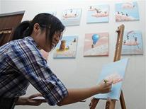 Painter MaryAnn Loo works next to her art pieces in her home during an interview in Singapore February 4, 2013. Some young Singaporeans feel a sense of disconnect from the traditional paths that are laid out ahead of them as part of this striving - get into a top school, land a high-paying job and hope that their children can build on their achievements. Picture taken February 4, 2013. REUTERS/Edgar Su