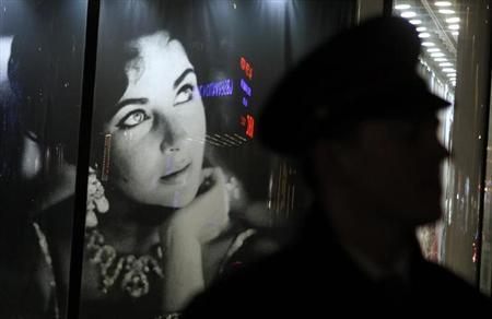 A security guard walks past an image of Elizabeth Taylor during an auction of the late actress' jewelry, clothing, art and memorabilia in New York, December 13, 2011. REUTERS/Carlo Allegri/Files