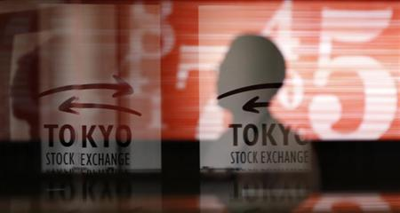 Men walk past logos at the Tokyo Stock Exchange in Tokyo February 6, 2013. REUTERS/Toru Hanai/Files