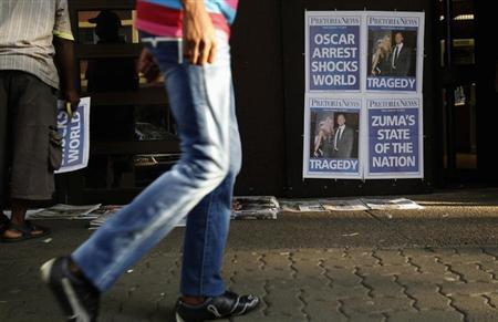 A man walks past posters of newspapers with a headline that refers to South African ''Blade Runner'' Oscar Pistorius at a newspaper stall outside court in Pretoria February 15, 2013. REUTERS/Siphiwe Sibeko