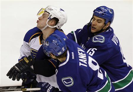 St. Louis Blues Vladimir Tarasenko (L) is checked by Vancouver Canucks Chris Tanev and Aaron Volpatti (R) during the second period of their NHL hockey game in Vancouver, British Columbia February 17, 2013. REUTERS/Ben Nelms