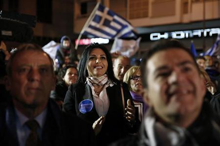 Supporters of Presidential candidate Nicos Anastasiades of the right wing Democratic Rally party watch election results on a screen outside the party's polling station in Nicosia February 17, 2013. REUTERS/Yorgos Karahalis