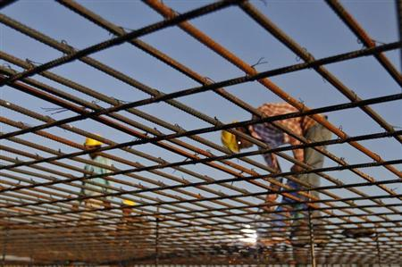 A worker welds iron rods at the construction site of a commercial complex in Ahmedabad November 29, 2012. REUTERS/Amit Dave/Files