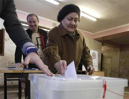 A woman casts her ballot at a polling station during the presidential election in Yerevan, February 18, 2013. REUTERS/David Mdzinarishvili