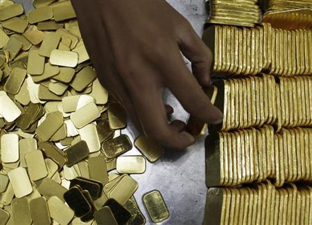An employee holds a gold piece, each weighing 100 grams, at the state-owned mining company PT Antam Tbk metal refinery in Jakarta July 13, 2012. REUTERS/Beawiharta/Files