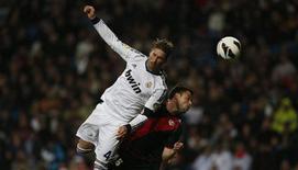 El Real Madrid sobrevivió a una temprana tarjeta roja de Sergio Ramos para imponerse a sus rivales locales del Rayo Vallecano por 2-0 el domingo en el Bernabéu, en una jornada en la que también ganaron sus partidos de Liga los líderes, el Barcelona, y su inmediato seguidor, el Atlético de Madrid. En la imagen, el madridista Sergio Ramos (I) lucha por un balón con Javi Fuego durante el partido de Liga contra el Rayo Vallecano en el Santiago Bernabéu, en Madrid, el 17 de febrero 2013. REUTERS/Javier Barbancho