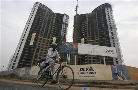 A man cycles past the construction site of a residential apartment building by property developer DLF Ltd. in Gurgaon January 27, 2010. REUTERS/Adnan Abidi/Files