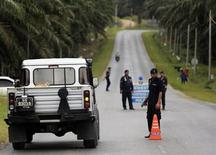 Malaysian policemen man a road block on a street leading to Kampung Tanduo, the area where the armed men are holding off, in Felda Sahabat outside Lahad Datu town on Borneo island February 18, 2013. About 100 armed men holed up in a village in the Malaysian state of Sabah are refusing to leave, saying they have links with the Sultanate of Sulu in the Philippines which has a historic claim over the northern tip of Borneo island. Malaysia police and army officials have formed a tight security ring around the village, media said, with navy boats patrolling nearby islands. The gunmen landed near the coastal town of Lahad Datu on Tuesday. REUTERS/Bazuki Muhammad