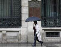 El saldo de los créditos morosos de la banca española bajó en 24.141 millones de euros en diciembre a 167.447 millones de euros, y la tasa de morosidad se redujo hasta el 10,44 por ciento desde un máximo del 11,38 por ciento en noviembre, según datos provisionales del Banco de España divulgados el lunes. En la imagen, un hombre con paraguas pasa junto a la sede del Banco Español de Crédito en el centro de Madrid el 28 de septiembre de 2012. REUTERS/Andrea Comas