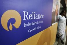 A woman walks past a poster of Reliance Industries installed outside the venue of the company's annual general meeting in Mumbai June 7, 2012. REUTERS/Vivek Prakash