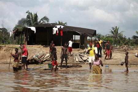 People wash and bathe in a village on the banks of the river Nun in Nigeria's oil state of Bayelsa November 27, 2012. REUTERS/Akintunde Akinleye