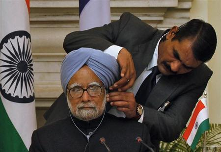 An official adjust the microphone of Prime Minister Manmohan Singh during the signing of agreements ceremony with France's President Francois Hollande in New Delhi February 14, 2013. REUTERS/B Mathur/Files