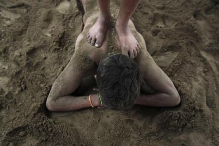 A wrestler stands on another's back after a fight at a permanent mud wrestling ring at ''Sia Ram bhajan samati akhaara'', a traditional Indian wrestling training centre, on the banks of the river Ganges in Kolkata February 17, 2013. REUTERS/Rupak De Chowdhuri
