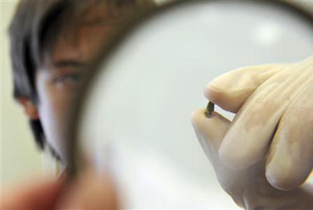 A research worker of the Ural Federal University inspects a fragment of a material substance in Yekaterinburg, the province of Sverdlovsk capital in the Ural Mountains, February 18, 2013. Scientists, representing the Ural Federal University, announced on Monday they managed to find elements of the meteorite in the district of the Cherbakul Lake near Chelyabinsk which was later confirmed during a research analysis at a laboratory, according to local media. A meteorite streaked across the sky and exploded over central Russia on Friday, raining fireballs over a vast area and causing a shock wave that smashed windows, damaged buildings and injured 1,200 people. REUTERS/Stringer