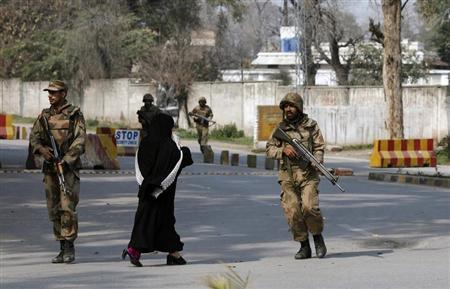 A woman walks past Pakistani army soldiers securing the area after gunmen raided the compound of a senior government official in Peshawar February 18, 2013. REUTERS/Fayaz Aziz