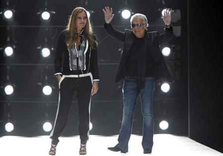 Italian designer Roberto Cavalli and his wife Eva acknowledge applause on the catwalk at the end of his Spring/Summer 2013 collection at Milan Fashion Week September 24, 2012. REUTERS/Alessandro Garofalo