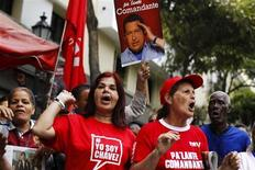 Поклонники венесуэльского лидера Уго Чавеса празднуют его возвращение с Кубы в Каракасе 18 февраля 2013 года. Чавес в понедельник неожиданно вернулся с Кубы более чем через два месяца после хирургической операции для лечения рака, чреватого завершением его 14-летнего правления южноамериканской страной-членом ОПЕК. REUTERS/Carlos Garcia Rawlins