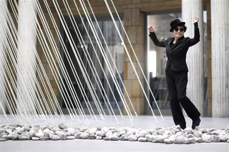 Japanese artist Yoko Ono dances next to art pieces ''river bed and morning beams'' during the opening of the exhibition ''Half-a-wind show. A retrospective'' at Schirn Kunsthalle in Frankfurt February 14, 2013. REUTERS/Lisi Niesner