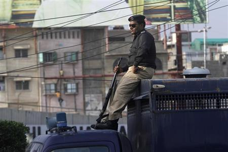 A police officer sits on the top part of a prison van while watching over a road during a protest in Karachi February 18, 2013. REUTERS/Athar Hussain (PAKISTAN - Tags: CRIME LAW POLITICS CIVIL UNREST RELIGION) - RTR3DY9Q