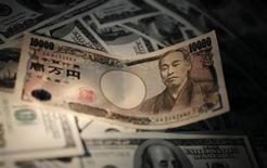 Un biglietto da 10.000 yen e banconote da 100 dollari. REUTERS/Yuriko Nakao