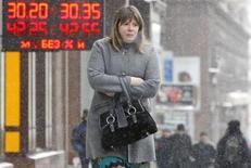 Женщина проходит мимо вывески пункта обмена валюты в Москве 29 января 2010 года. Рубль в понедельник торговался с минимальными изменениями на границе интервенционных покупок валюты центробанком, выступающей поддержкой бивалютной корзине; на поле рубля играли высокие нефтяные цены и текущий курс доллара США, приемлемый для экспортеров в налоговый период. REUTERS/Denis Sinyakov