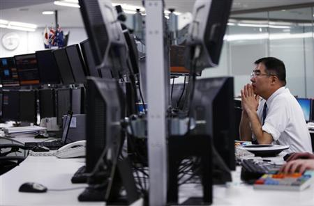 An employee of a foreign exchange company looks at monitors in Tokyo February 12, 2013. REUTERS/Toru Hanai