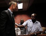 Velocista paralímpico, Oscar Pistorius, é escoltado pela polícia durante sua apresentação a um tribunal em Pretoria. O atleta sul-africano cancelou a participação em todas as provas previstas para os próximos meses para concentrar-se em sua defesa da acusação de homicídio, disse o agente do velocista. 15/02/2013 REUTERS/Siphiwe Sibeko