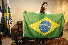 Blogueira cubana Yoani Sánchez, mais conhecida ativista de oposição do país, exibe bandeira brasileira após chegar no Aeroporto Internacional de Guararapes, no Recife. Sanchez foi recebida com protestos ao desembarcar nesta segunda-feira no Brasil, a primeira parada de uma viagem por diversos países após ter sido finalmente autorizada a deixar a ilha. 18/02/2013 REUTERS/Helia Scheppa