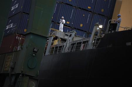 Container terminal operators work next to containers on a cargo ship at Brazil's main ocean port in Santos city September 20, 2012. REUTERS/Nacho Doce