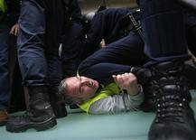Al menos dos personas fueron detenidas el lunes en el aeropuerto madrileño de Barajas en la primera de una larga serie de jornadas de huelga convocada por los trabajadores de Iberia que obligó a cancelar más de 80 vuelos tras recolocar a gran parte de los pasajeros. En la imagen, un trabajador de Iberia arrestado por la policía en Barajas el 18 de febrero de 2013. REUTERS/Sergio Pérez