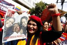 A supporter of Venezuela's President Hugo Chavez holds a picture of him as she takes part in a gathering at Plaza Bolivar in Caracas February 18, 2013. Chavez made a surprise return from Cuba on Monday more than two months after surgery for cancer that has jeopardized his 14-year rule of the South American OPEC member. The 58-year-old socialist leader underwent a six-hour operation in Cuba on December 11 and had not been seen or heard in public until photos of him were published on Friday. REUTERS/Carlos Garcia Rawlins (VENEZUELA - Tags: POLITICS)