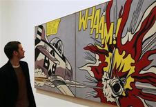 A worker poses with pop artist Roy Lichtenstein's Whaam!, 1963, during a media viewing of the Lichtenstein: A Retrospective exhibition, at Tate Modern in London February 18, 2013. The exhibition which opens on February 21 runs until May 27. REUTERS/Luke MacGregor