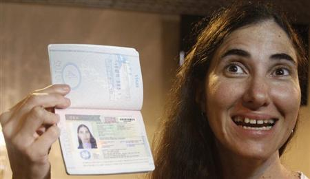 Cuba's best-known dissident, blogger Yoani Sanchez poses with her passport after arriving at Guararapes International airport in Recife February 18, 2013. Sanchez, was granted a passport two weeks ago under Cuba's sweeping immigration reform that went into effect this year, after being denied permission to travel more than 20 times over the past five years. REUTERS/Helia Scheppa