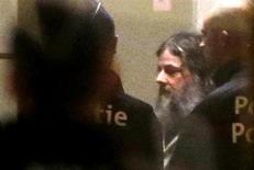 Marc Dutroux escorté par la police dans un Palais de justice, à Bruxelles. La justice belge a rejeté lundi une demande de mise en liberté conditionnelle du pédophile, l'estimant incapable de se réinsérer dans la société. /Photo prise le 4 février 2013/REUTERS/Francois Lenoir