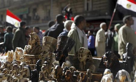 Pharaonic figurines are pictured as protesters, who oppose Egyptian President Mohamed Mursi, shout slogans during a demonstration against him and members of the Muslim Brotherhood at Tahrir Square in Cairo February 15, 2013. REUTERS/Amr Abdallah Dalsh