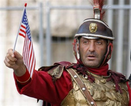A man dressed as a Roman centurion, who makes his living posing with tourists outside the ancient Colosseum, holds an American flag while posing with supporters of U.S. President-elect Barack Obama attending a victory rally in Rome November 8, 2008. REUTERS/Chris Helgren