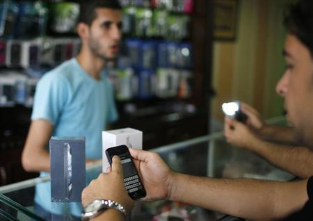 A Palestinian customer holds Apple's new iPhone 5 at a mobile phone store in Gaza City October 16, 2012. REUTERS/Mohammed Salem/Files