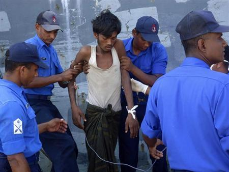 Sri Lanka's navy soldiers assist an injured Myanmar national to a navy ship in Galle February 17, 2013. The navy said it rescued rescued 32 Myanmar nationals who were stranded after their wooden vessel begun to sink in the deep seas off the eastern coast. Picture taken February 17, 2013. REUTERS/Stringer