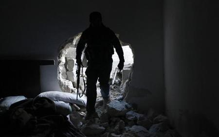 A Free Syrian Army fighter walks through a damaged apartment near Al Neirab airport in Aleppo February 17, 2013. REUTERS/Hamid Khatib