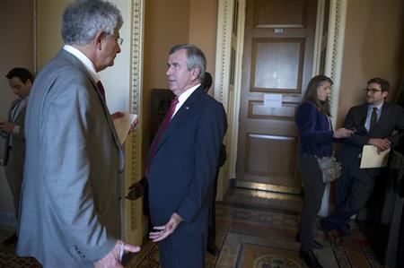 Sen. Mike Johanns (D-NE) (2nd L) speaks to reporters after leaving the Mansfield Room following a caucus meeting at the U.S. Capitol in Washington December 30, 2012. REUTERS/Mary Calvert