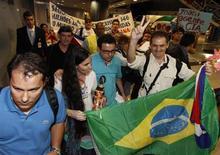 Yoani Sánchez, la cara más conocida de la disidencia cubana, fue recibida el lunes en Brasil por un pequeño grupo de partidarios del gobierno comunista de la isla que le llamaron agente de la CIA, en la primera escala de una gira internacional. En la imagen, Sánchez camina entre partidarios tras llegar al aeropuerto de Guararapes mientras unos manifestantes protestan al fondo, el 18 de febrero de 2013. REUTERS/Helia Scheppa